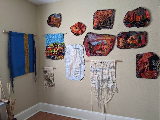 Several fiber artworks on the walls in the studio