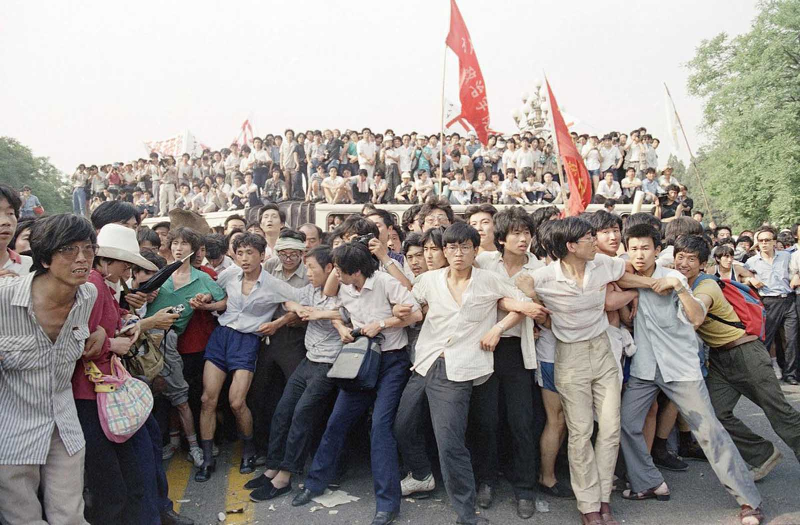 Pro-democracy protesters link arms to hold back angry crowds, preventing them from chasing a retreating group of soldiers near the Great Hall of the People, on June 3, 1989 in Beijing. Protesters were angered by an earlier attack upon students and citizens using tear gas and truncheons. People in the background stand atop buses used as a roadblock.