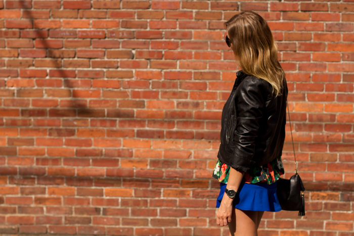 Vancouver Fashion Blogger, Alison Hutchinson, is wearing a Forever 21 black leather jacket, urban outfitters floral loose peplum top, an electric blue flare skirt from choies, black ankle boots from urban outfitters, a purple bangle from bauble bar, and a black leather bag from H&M