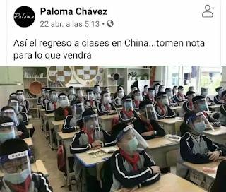 Niños chinos en la clase del colegio con mascarillas y pantallas