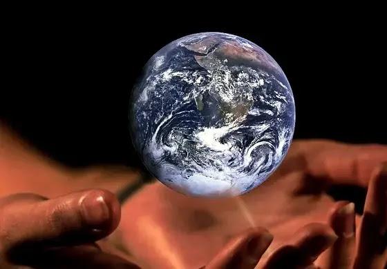 A imagem mostra o planeta terra flutuando no universo sobre mãos de um ser celestial.
