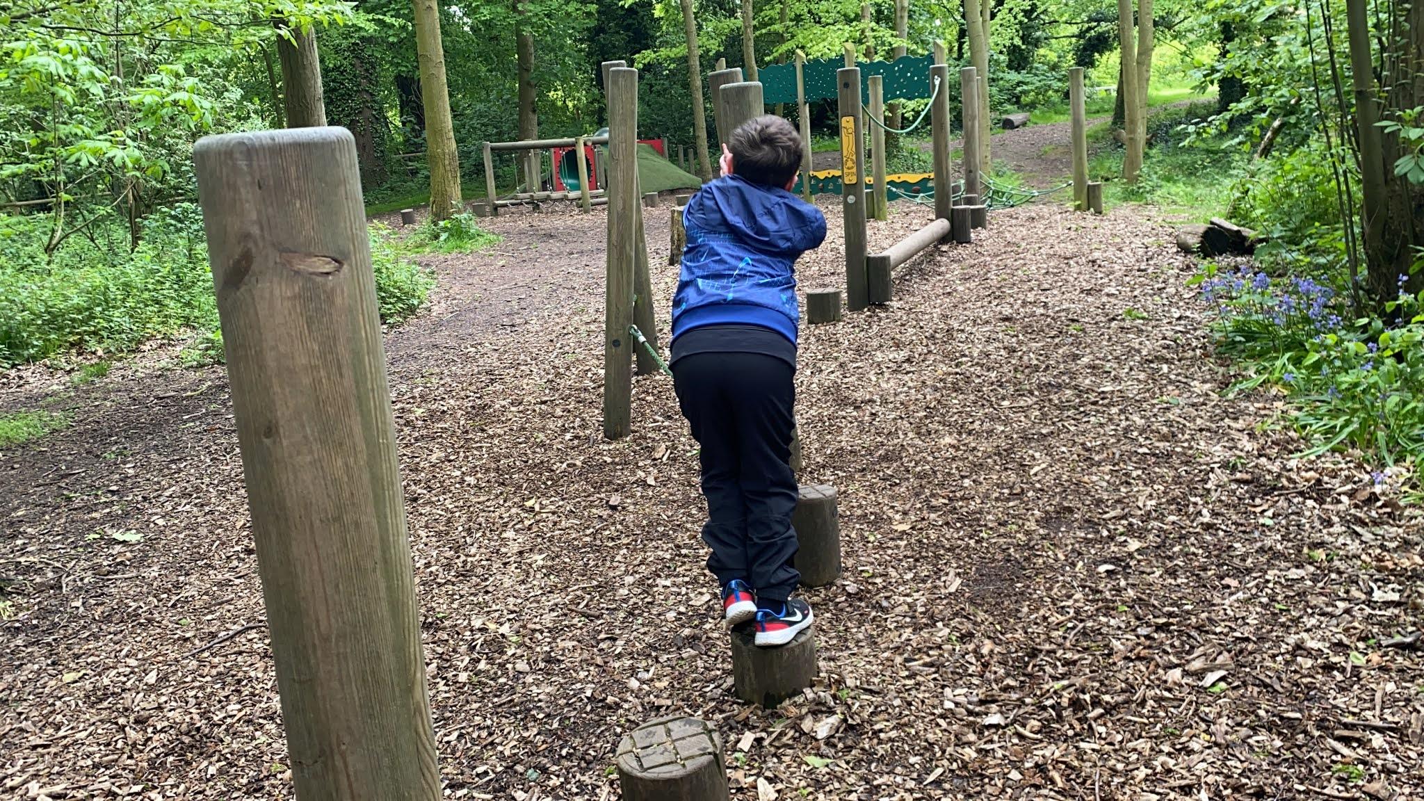 boy playing at a woodland playground
