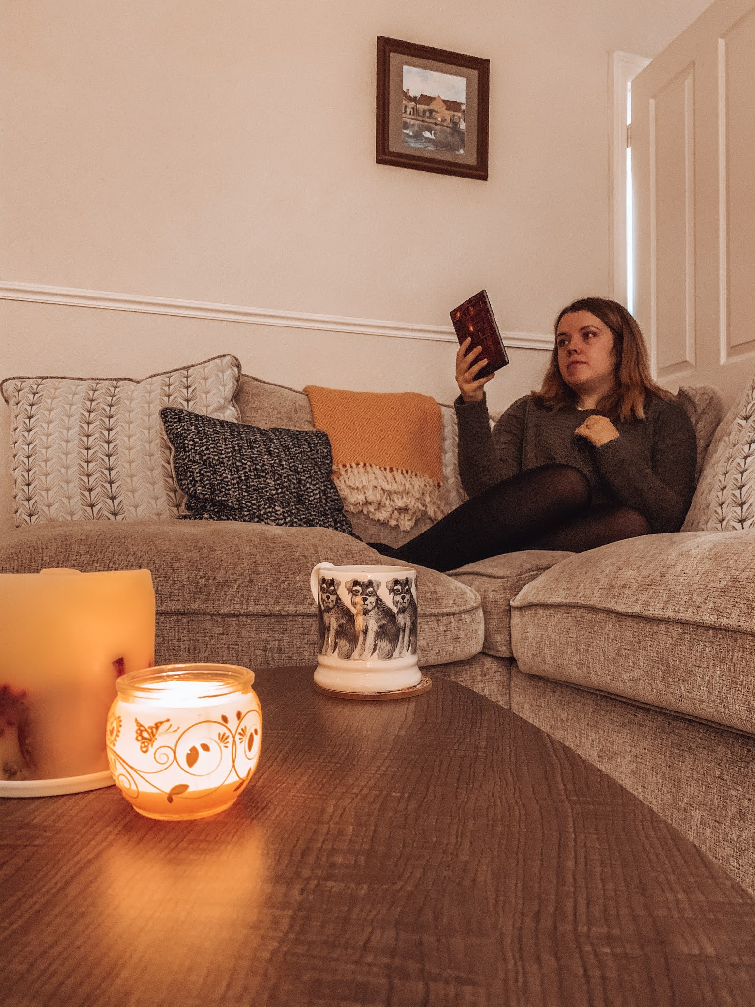 In the foreground is a walnut coffee table with two candles lit, and a mug of tea. Behind this Jess sits on a cream/grey speckled sofa, featuring lots of cushions and an orange tasseled blanket. Jess is holding her kindle and wearing a green knitted jumper over a skirt and tights.