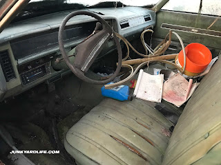 Green interior of 1974 Chevrolet Caprice Estate station wagon includes a bench seat and has become a makeshift storage container.