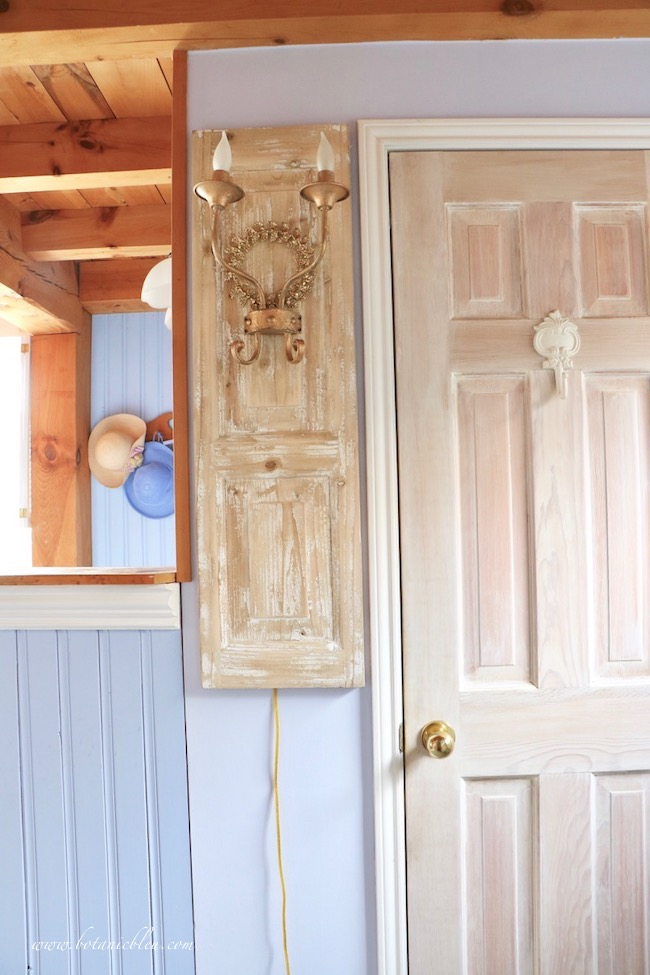 French wood panel double metal sconce in master bath after makeover with plug in cord