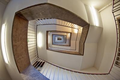 imagen que muestra una escalera de caracol fotografiada desde abajo. Semeja el dibujo propio de una concha de caracol