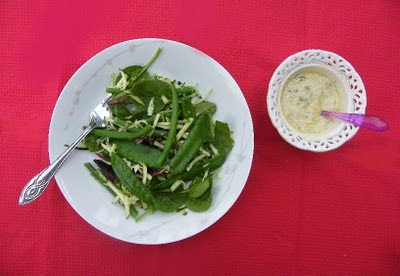 Green bean salad in a white bowl next to a small bowl of creamy lemon, cumin and coriander dressing