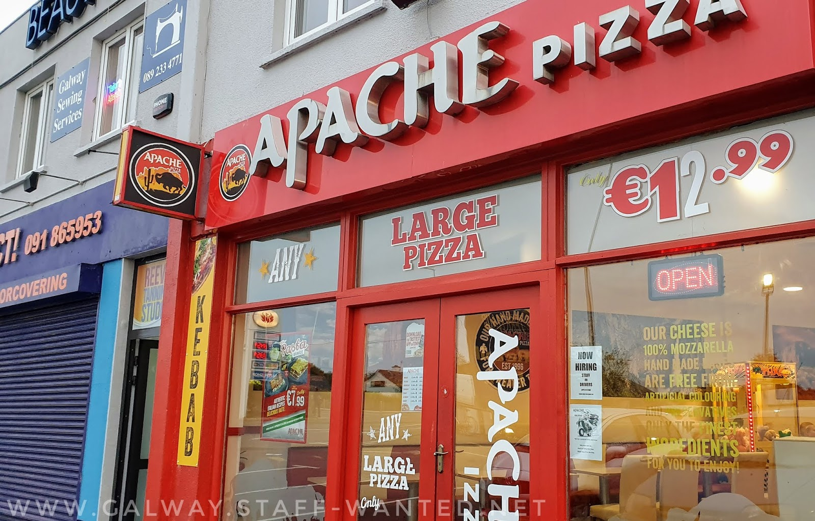 Apache pizza shopfront - our cheese 100% mozzarella, hand-made pizza base are free from artificial colouring and preservatives - red LED open sign - large pizza for €12.99
