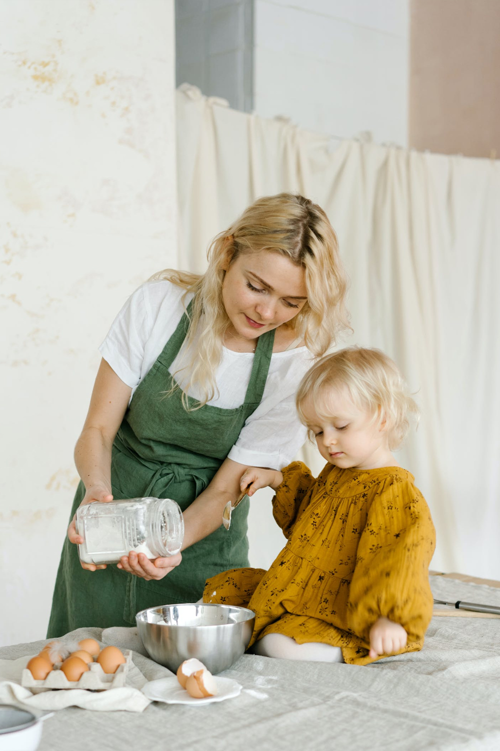mother and her daugther wearing cottagecore inspired looks are cooking in the kitchen.