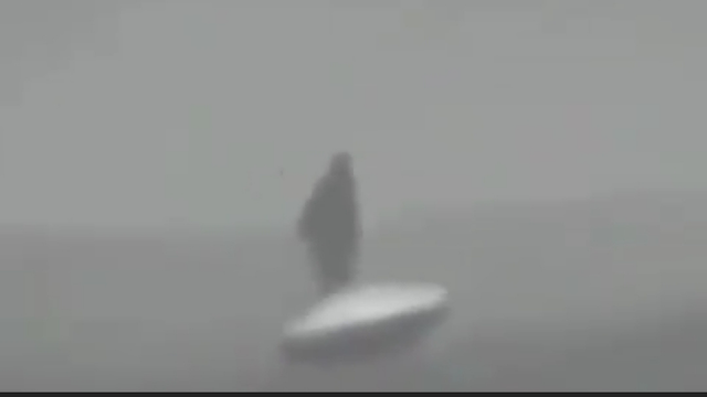 A man in black looking at the UFO in Siberia and is filmed covertly or they know.