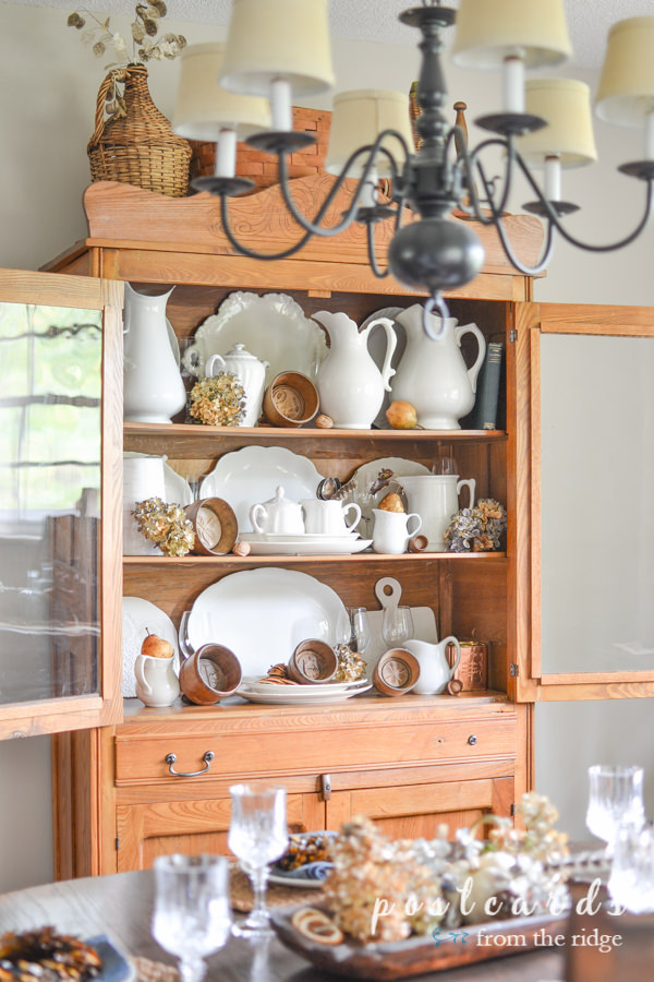 antique oak hutch with vintage wooden butter molds, white ironstone pitchers and platters, and dried hydrangeas