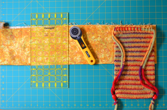 Fabric folded horizontally and laid out onto cutting mat.  The fold is at the bottom edge and is lined up with the mat's grid.  A quilter's rule is lined up with the fabric fold and the grid indicating where the fabric needs to be cut.  The rotary cutter is pointing to that line.  The bag is laid out on top of the fabric to show how the fabric is at least twice as wide as the bag.