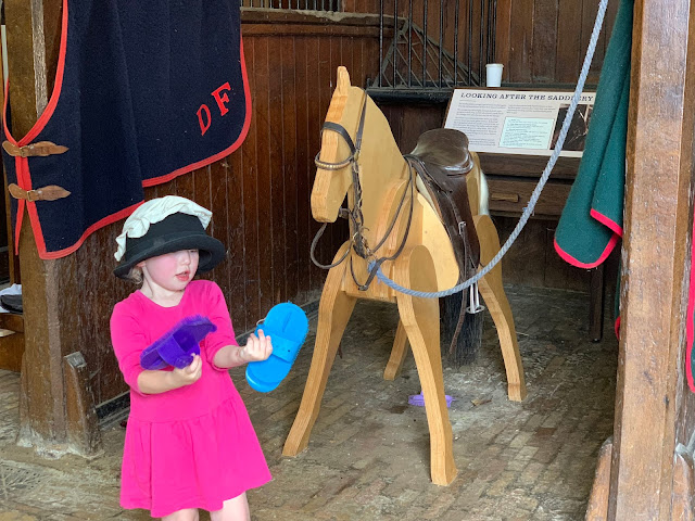 A toddler holding 2 horse brushes with a hat and clothcap on her head standing in a stables with a wooden horse next to her