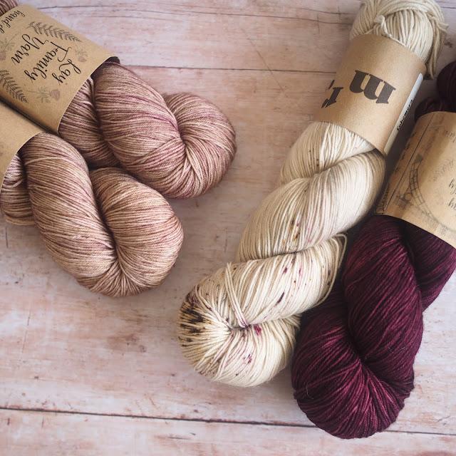 4 hanks of yarn including 2 coffee-coloured, 1 beige and 1 burgundy