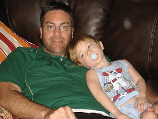 A photo of David Brodosi and his son lounging on the couch