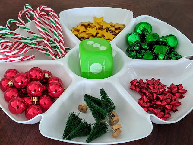 white divided tray with plastic candy canes, green jingle bells, red mini ornaments, gold stars, mini Christmas trees, green foam dice and red mini bows