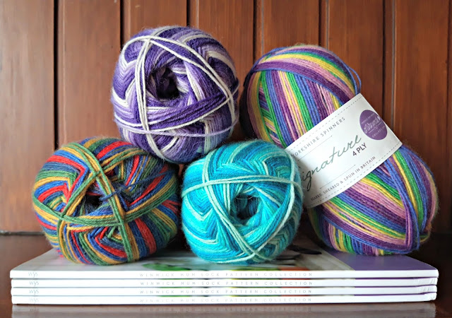 A photo showing four balls of Winwick Mum yarn balanced on some Winwick Mum Collection pattern books.  There is a panelled wooden wall in the background and the books are resting on a wooden mantelpiece