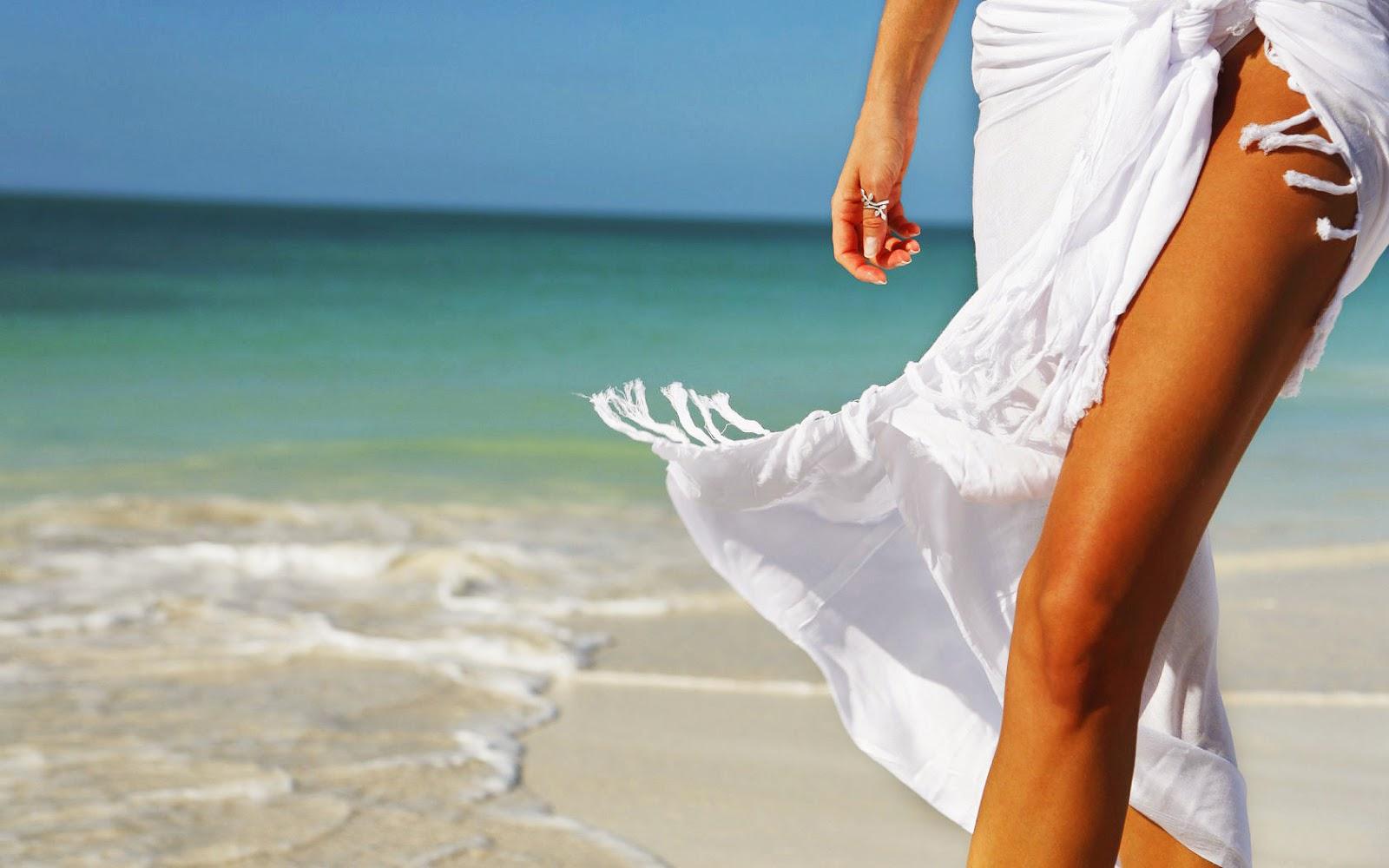 Foto met strand, zee en vrouw in witte jurk