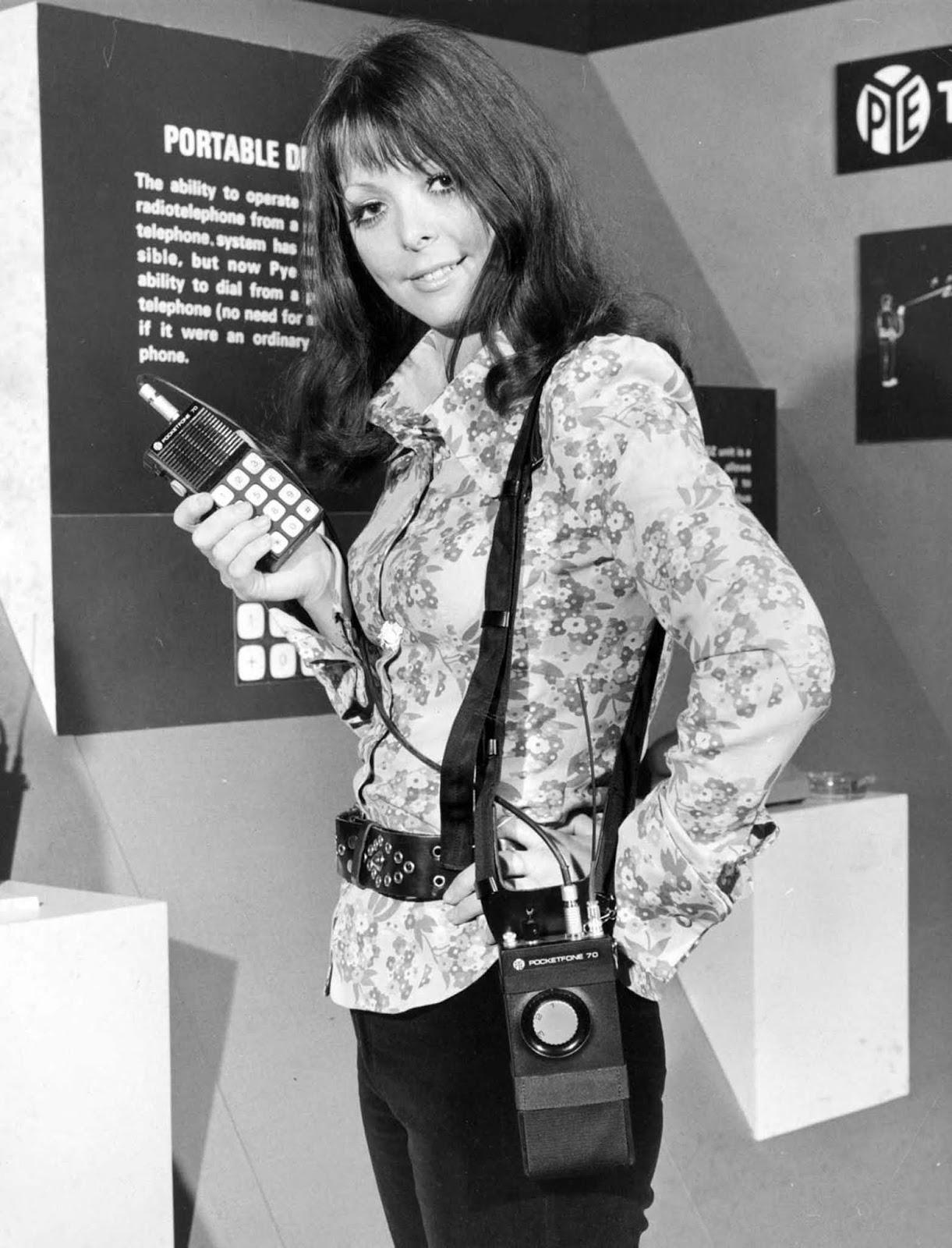 """O rádio-telefone portátil era um precursor do telefone celular. Funcionava discando para sistemas telefônicos. Aqui, um modelo exibe um cenário na exposição """"Communications Today, Tomorrow and the Future"""" no Royal Lancaster Hotel, London. 1973."""