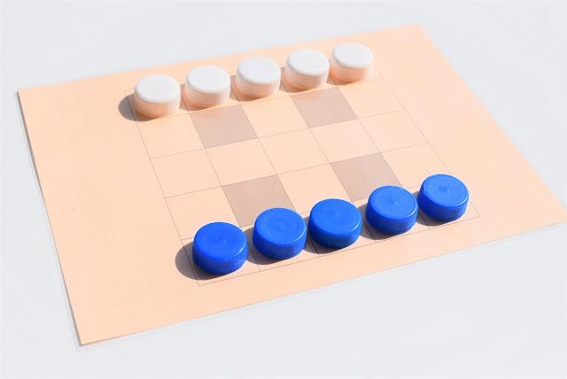 na zdjęciu plansza 5x5 pól w kolorze pomarańczowym, cztery pola są zamalowane i wyłączone z gry, w pierwszym rzędzie po jednej stronie stoi pięć nakrętek w kolorze niebieskim a po drugiej stronie pięć nakrętek w kolorze białym