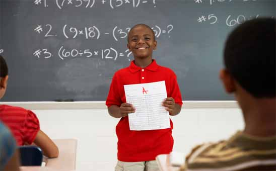 A black boy standing in front on a class with a test paper in his hands