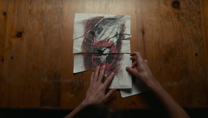 Imagem: uma mesa com um papel rasgado em pedaços e um par de mãos colocando os pedaços um ao lado do outro e no papel pode-se ver um desenho infantil em vermelho e preto de um enorme monstro de dentes afiados devorando um garotinho.