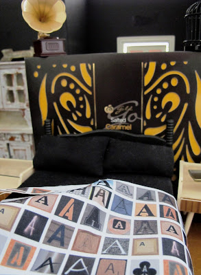 Modern black dolls' house miniature bed set in a room set up in dark shades of black, brown and cream.