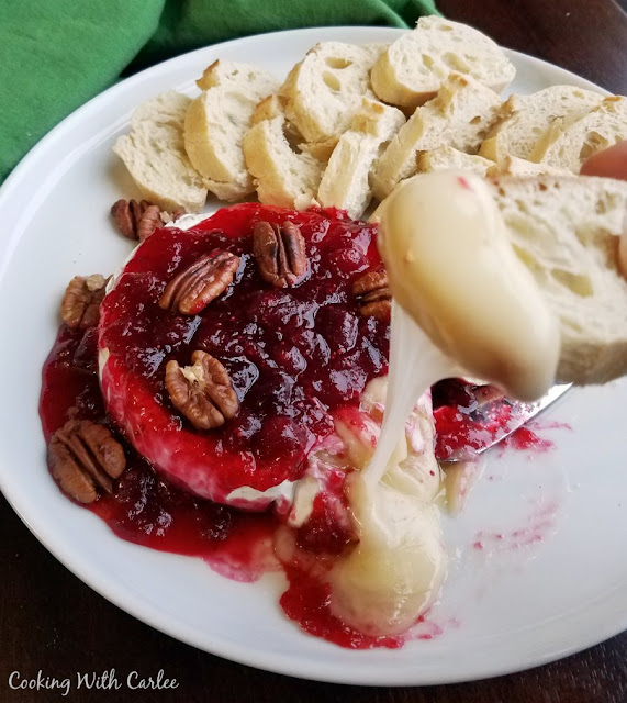 plate of baked brie with cranberry sauce and pecans with baguette slice dipped in gooey cheese