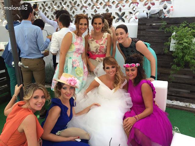 Grupos de invitadas con la novia el día de su boda, entre ellas invitada con mono azul klein y tocado tipo sombrero con velo plumetti