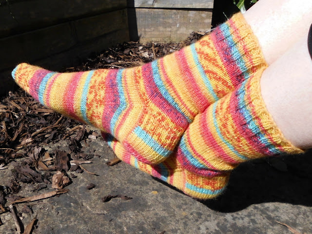 A pair of orange striped socks being modelled on feet in the sunshine