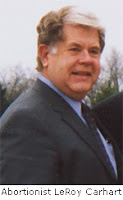 Candid outdoor shot of an overweight middle-aged man with his hair going white in the front. He is wearing a suit and tie.