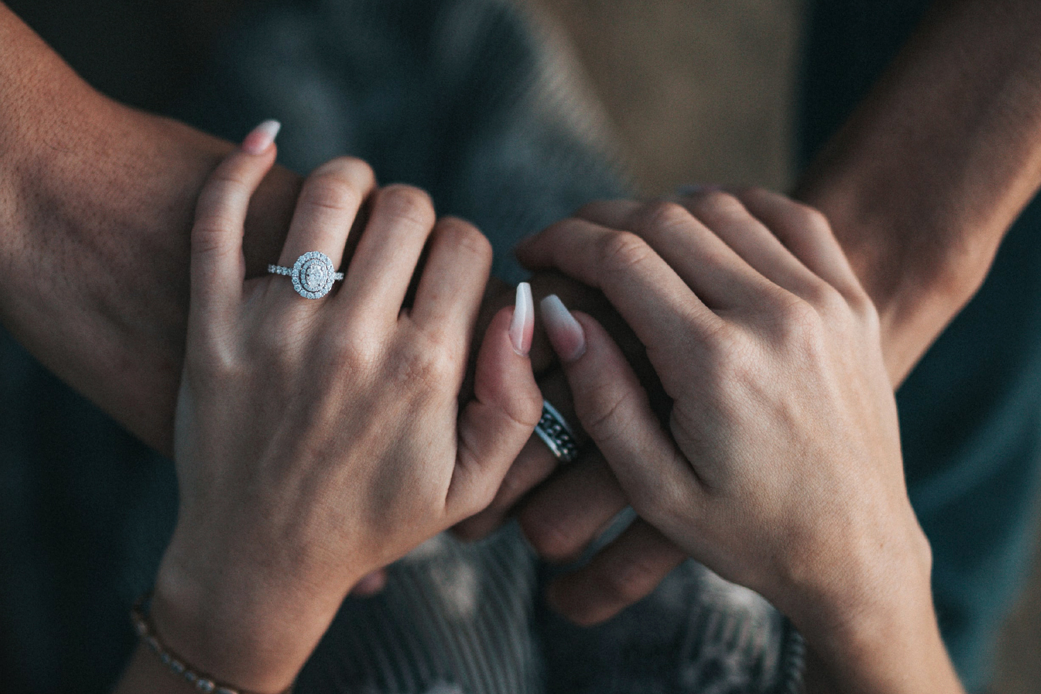 a close up picture of man's and women's hands, a man put an engagement ring on her finger