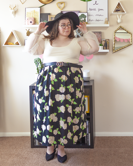 An outfit consisting of a black wide brim floppy hat, a cream blouse with sheer balloon sleeves tucked into a black floral maxi skirt and black pointed toe slingback flats.