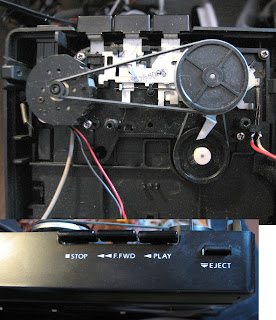 [Image: The cassette player opened, showing the tape drive mechanism with several wheels connected to each other via rubber strings, and the control buttons connected to them via springs and levers.]