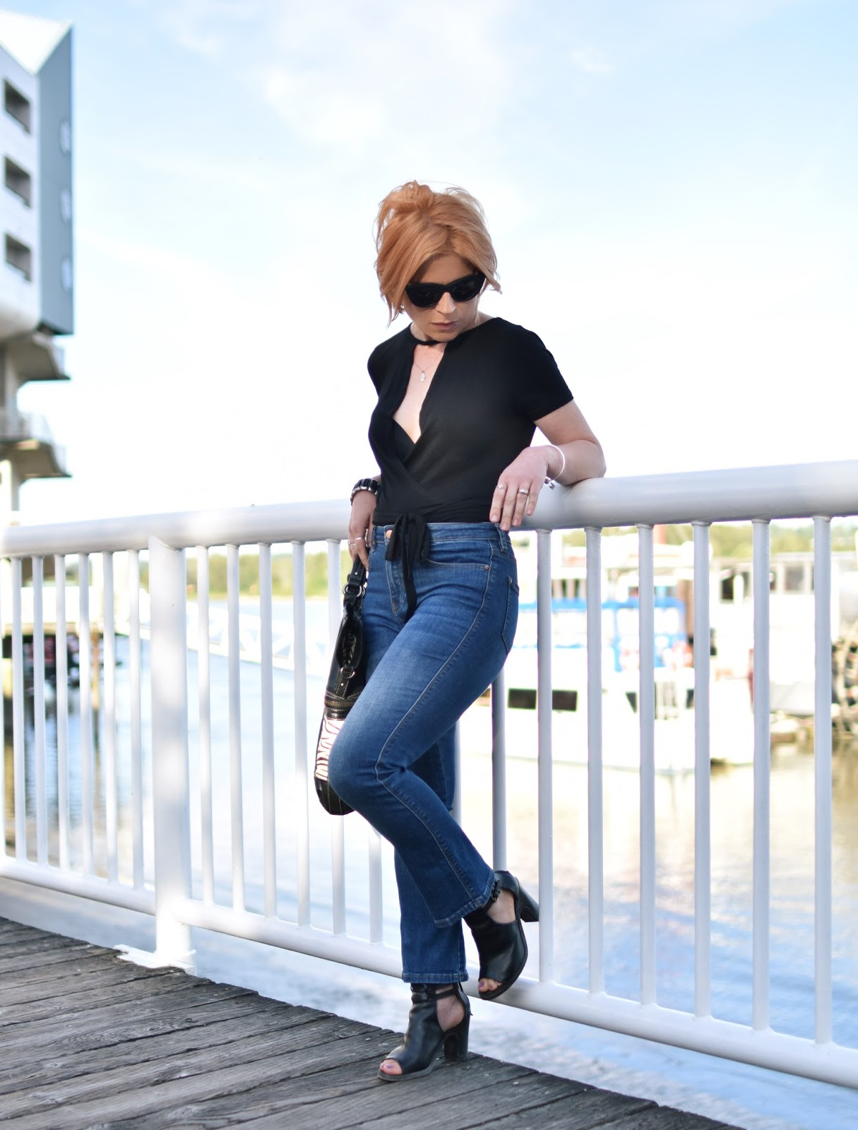 styling a short-sleeved wrap top with cropped flare jeans, cut-out booties, and cat-eye sunglasses