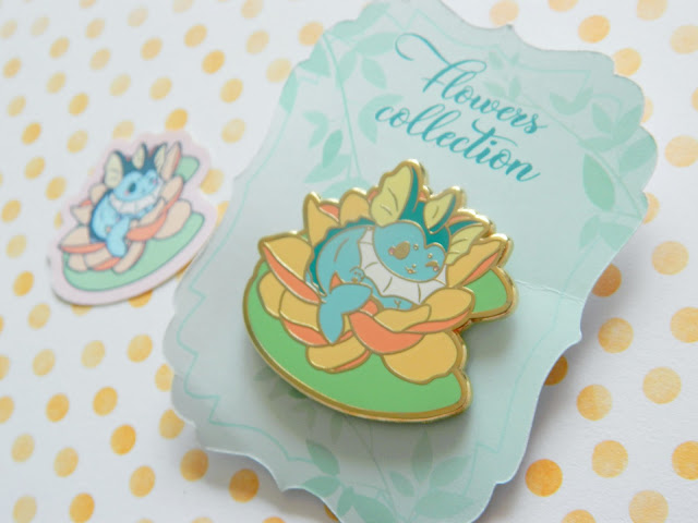 A photo of a pokemon eeveelution pin designed by Quirkory, vaporeon, a blue pokemon, is sitting on a orange yellow lotus flower