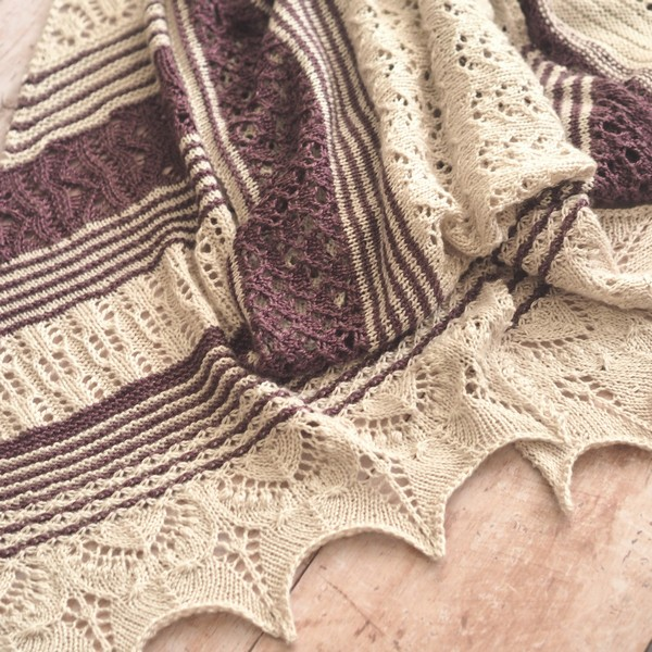 cream and mulberry lace wrap piled up on a wooden floor