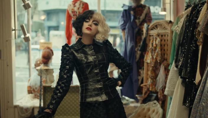 Imagem: cena do live-action de Cruella com os cabelos pretos e brancos, em um vestido preto de couro com detalhes quadriculados pretos e cinza-escuros, apoiada em uma bengala em uma loja de roupas cercada de manequins com diversos vestidos ao redor.