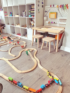 wooden train track on playroom floor