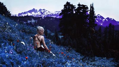Chica sentada encima de flores con montaña morada de fondo