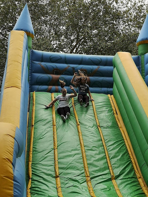 Tween girls having fun on an inflatible slide
