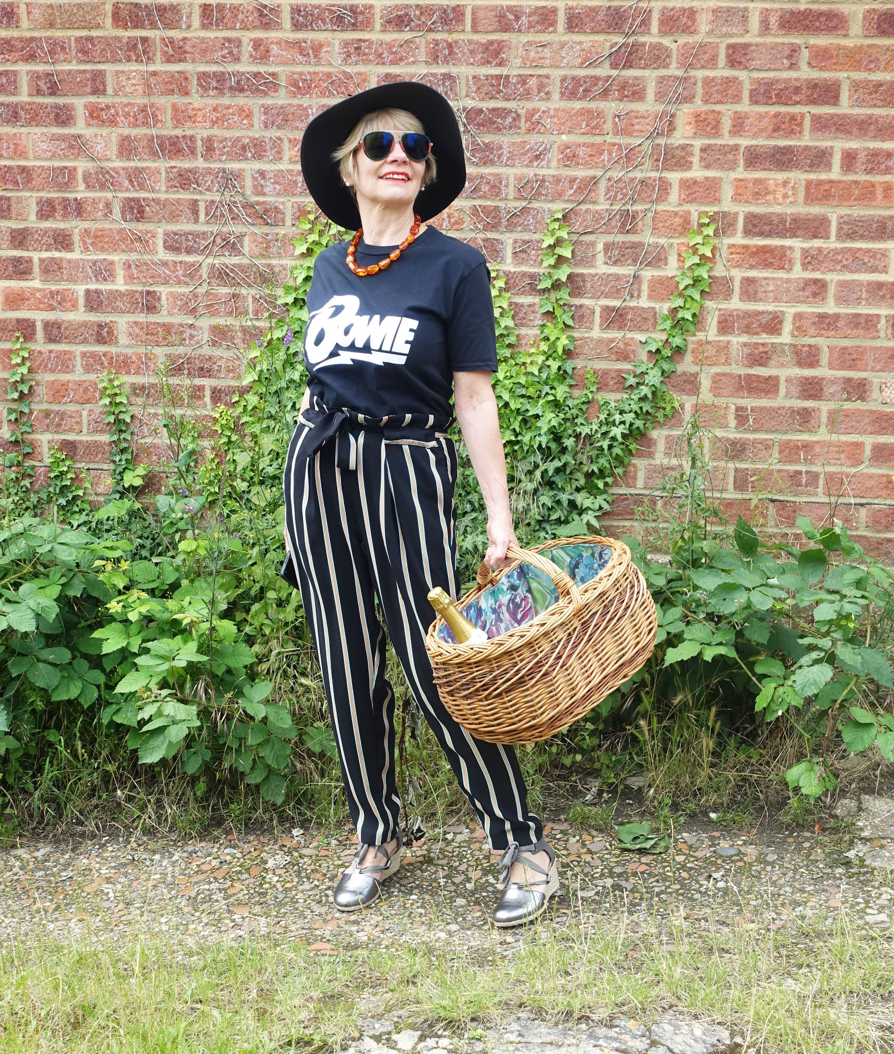 Trousers or shorts are great for a picnic where sport might be involved. Is This Mutton's Gail Hanlon is wearing striped paperbag trousers with a Bowie t-shirt, Tilley hat and Gucci prescription sunglasses