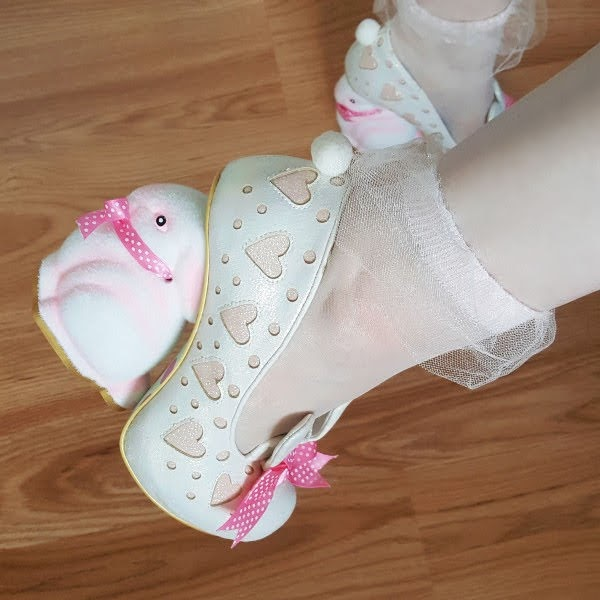 close up of bunny heeled shoe on foot with heart detailing and pom pom