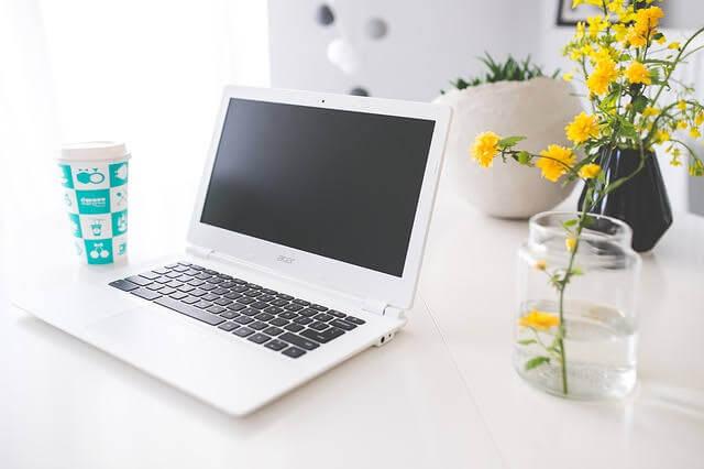 自宅のテーブルでパソコンを開いている写真