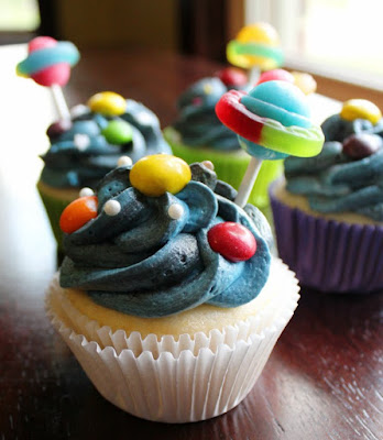 cupcakes with blue and black frosting, candy planets and sucker saturns