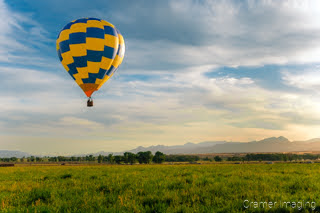 Cramer Imaging's fine art photograph of a yellow and blue hot air balloon taking flight in Panguitch Utah with a blue partly cloudy sky