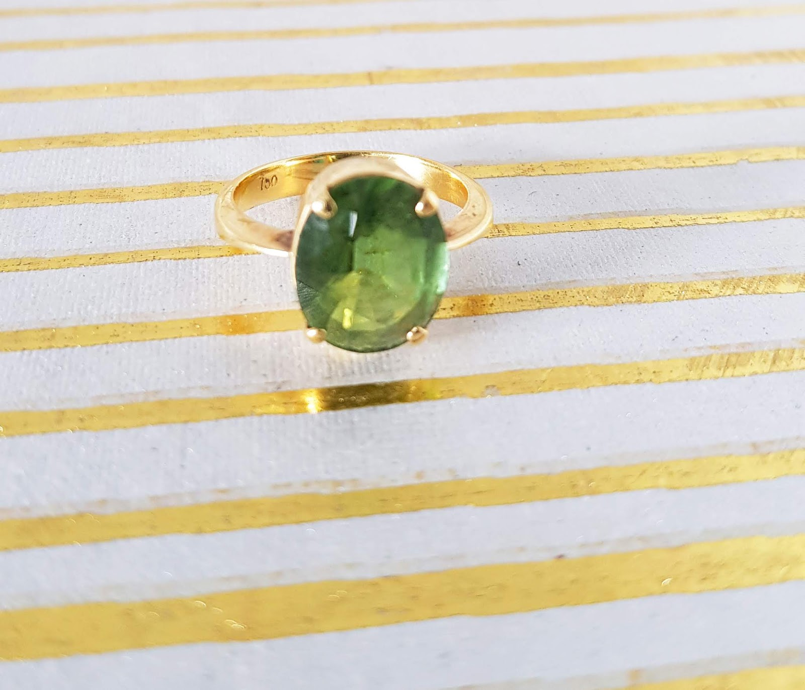 Close-up of a green tourmaline from Sri Lanka set in 18 ct yellow gold.