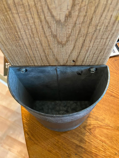 Photo of a metal wall container screwed into a cutting board.