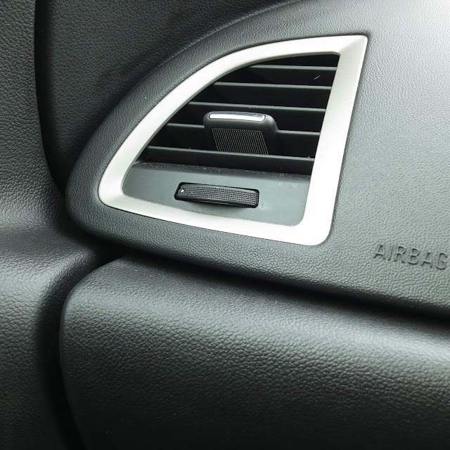Adjustable air vent and airbag case in passenger side of car.Black and silver.