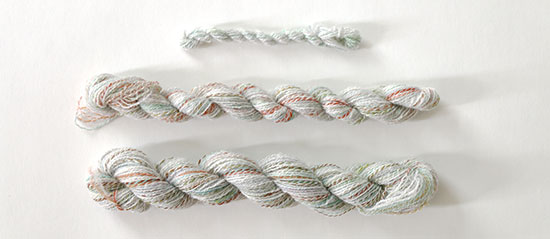 Three skeins of various sizes of light-colored handspun wool and alpaca yarn with bright colors mixed in, lined up horizontally on a white background.